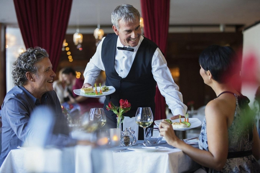 Waiter serves food for customers